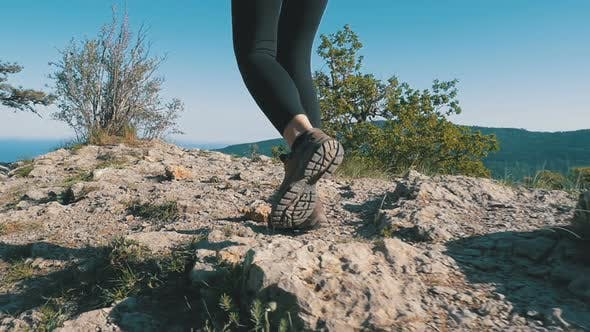 Thumbnail for View on Feet of Traveler Woman Hiking Walking on the Top of Cliff in Mountain. Slow Motion
