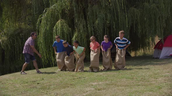 Thumbnail for Kids at summer camp in gunny sack race