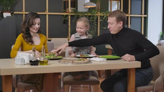 Thumbnail for Cheerful Man Putting Pizza on Plates of Family in Restaurant