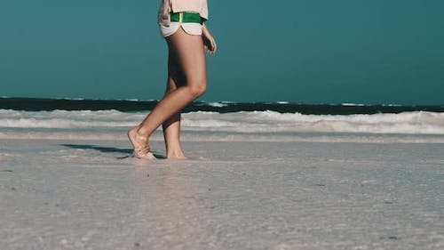 Legs of Young Woman Walking By White Sand Paradise Beach with Tidal Ocean Waves