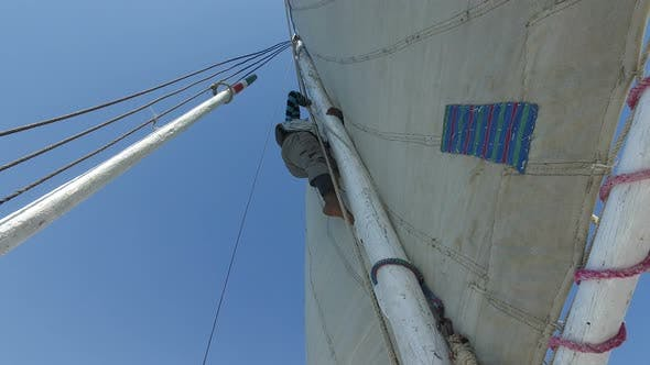 Thumbnail for Nubian felucca sailing crew climbing on top of felucca