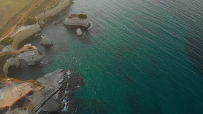 Aerial Focused Shot of Deep Green Waters By the Edge of the Cliff