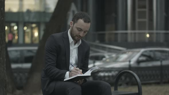 Cover Image for Young Bearded Business Man Thinking and Wrighting Notes at Green Park, Traffic Behind