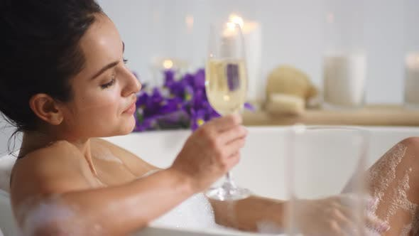 Sexy Woman Washing Legs with Foam in Bath. Girl Drinking Champagne in  Bathtub by stockbusters on Envato Elements