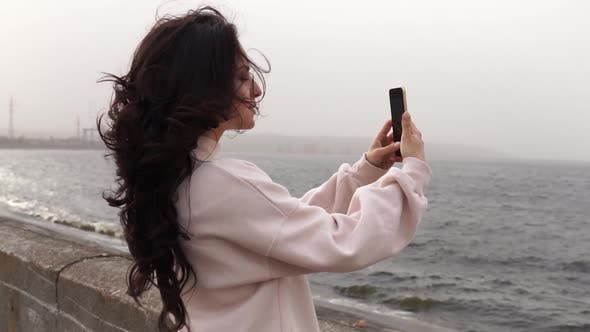 Thumbnail for Beautiful woman takes pictures of the sea with her phone