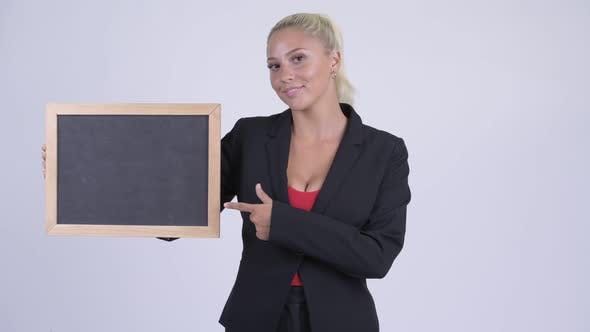 Cover Image for Young Happy Blonde Businesswoman Holding Blackboard and Giving Thumbs Up