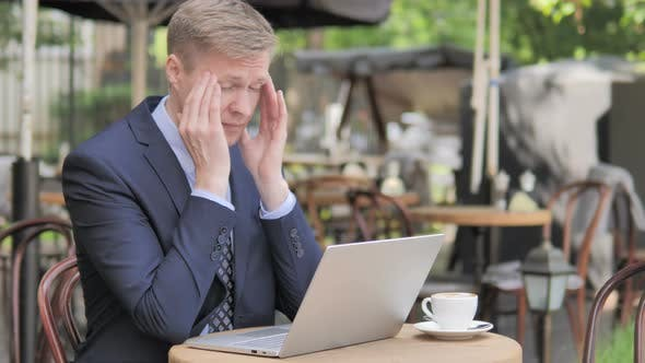 Thumbnail for Businessman with Headache Using Laptop in Outdoor Cafe
