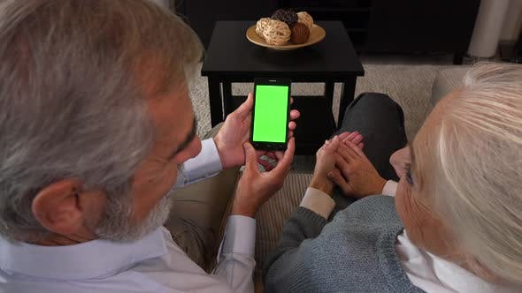 Thumbnail for An Elderly Couple Sits on A Couch in An Apartment and Looks at A Smartphone with A Green Screen