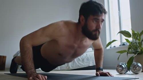 Shirtless Guy trainiert Push-Ups auf dem Boden zu Hause, Nahaufnahme