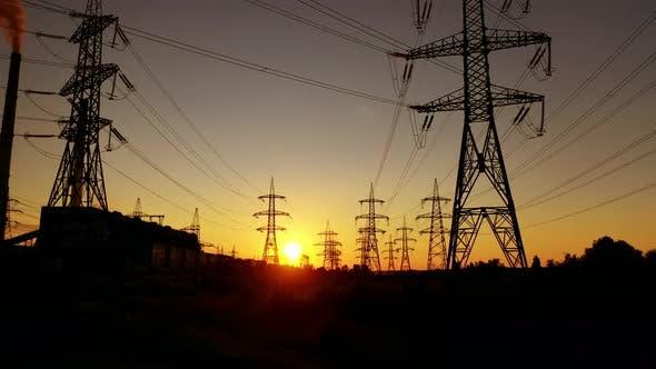 Transmission towers at orange sunset