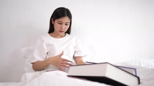 Asiatische junge Frau liest ein Buch auf dem Bett