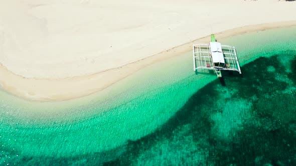 Thumbnail for Tropischer Strand aus weißem Sand, Draufsicht. Touristenboot vor der Küste. Ruhige Strand-Szene.