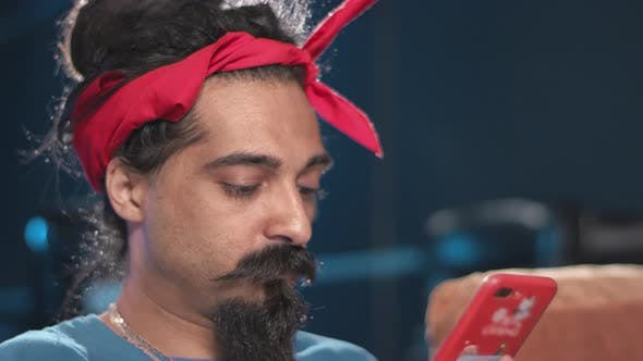 Thumbnail for Hindu with dreads, red handkerchief on head plays games on smartphone