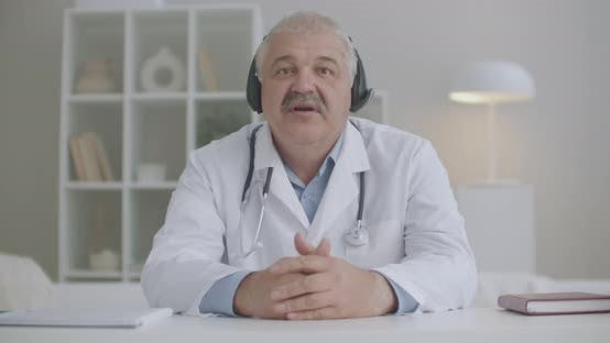 Male Cardiologist Is Consulting Online, Sitting in Office of Clinic and Answering To Patient By