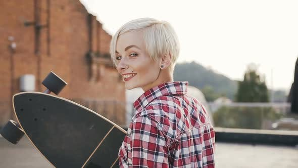 Thumbnail for Beautiful Blonde Girl Walking with Long Skateboard on the Modern Building Roof