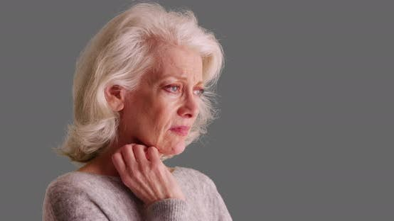 Unhappy older woman with sad pensive expression sighing on grey background