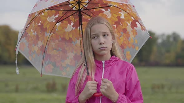 Thumbnail for Sad Caucasian Girl with Blonde Hair and Light Brown Eyes Dressed in Pink Jacket Holding Collorful