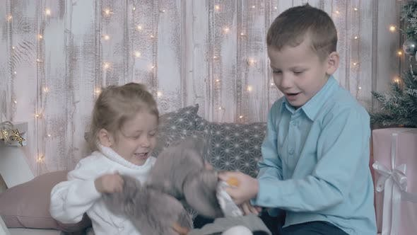 Happy Children Fight with Favourite Toys on Cozy Sofa