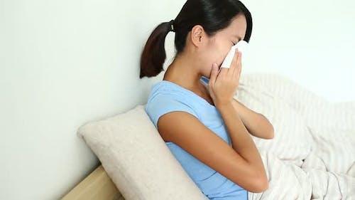 Woman sneezing on tissue