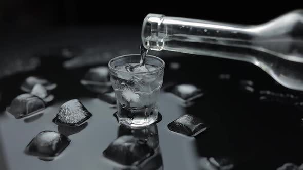 Thumbnail for Pouring Up Shot of Vodka Into Glass. Black Background. Pour of Alcohol Drink