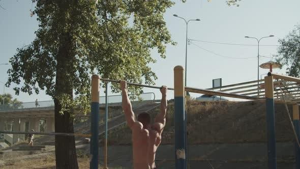 Thumbnail for Shirtless Fit Man Doing Backflip on Horizontal Bar