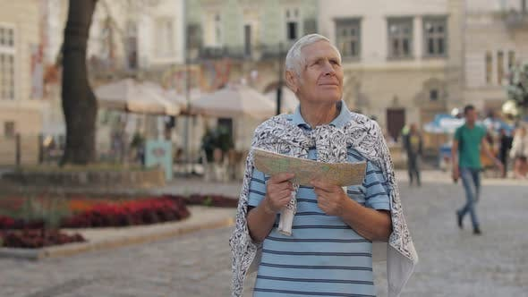 Thumbnail for Senior Male Tourist Exploring Town with a Map in Hands. Looking for the Route