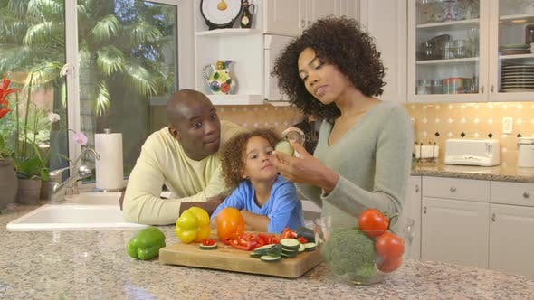 Thumbnail for African American family  chopping vegetables in kitchen
