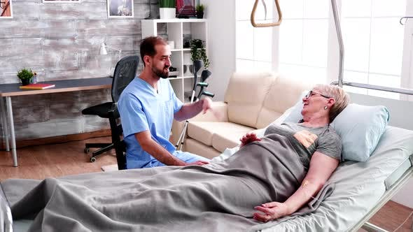Male Nurse Visit Old Woman Lying in Bed