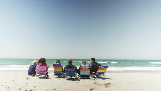 Thumbnail for Group of friends hanging out sitting at the beach