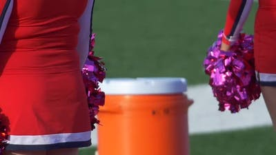 Detail of high school cheerleaders cheering with their pom-poms at a football game.