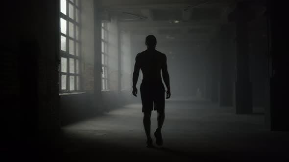 Man Silhouette Walking in Dark Corridor
