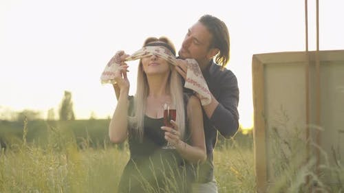 Beautiful Caucasian Woman Standing with Wineglass on Sunny Meadow As Handsome Man Closing Her Eyes