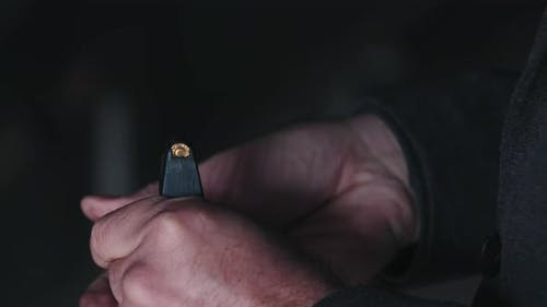 A Man Sticks Bullets Into a Gun Magazine