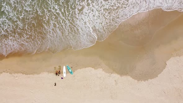 Aerial Top Down View of Waves Brushing the Sand and Surfers with Surfboard Sitting on the Seashore