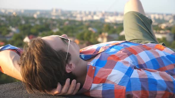 Handsome Man in Sunglasses Lying on Roof with Cityscape at Background