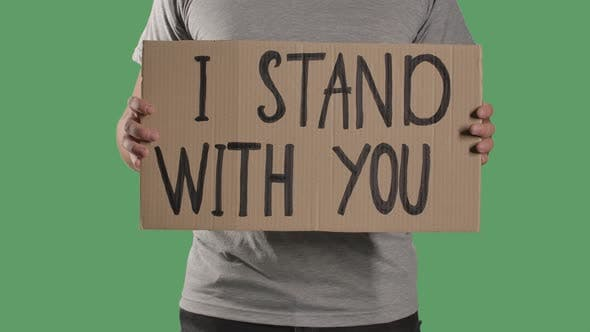 Thumbnail for Man Holds in Front of Him a Poster From a Cardboard Box with the Words I STAND WITH YOU. Protest