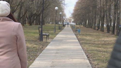 Mann stiehlt im Park eine Damentasche von einer Bank