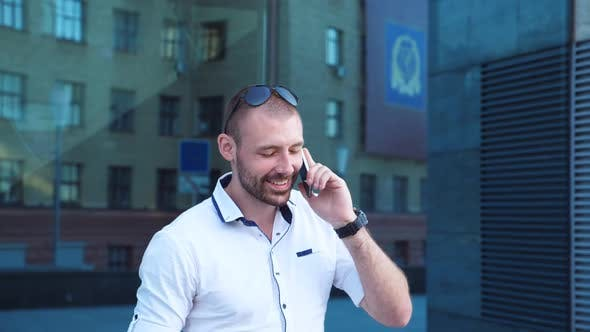 Handsome Businessman Talking on Phone Near Office and Having Positive Emotions