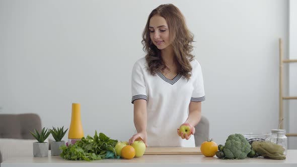 Young Skill Woman Puts Apples on the Table While Standing in Modern Kitchen