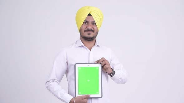 Thumbnail for Happy Bearded Indian Sikh Businessman Showing Digital Tablet