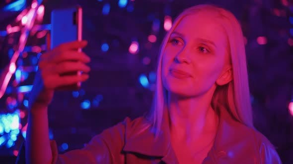 Sweet Woman Using Mobile Phone at Night Club Party