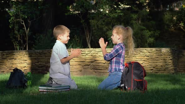 Thumbnail for Merry Schoolkids Playing Clapping Game Sitting on Grass After Learning on School Break