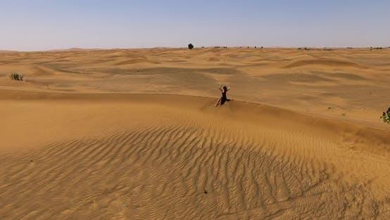 Girl Sitting on a Dune in the Desert