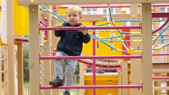 Thumbnail for Cute Little Boy Climbing On A Jungle Gym