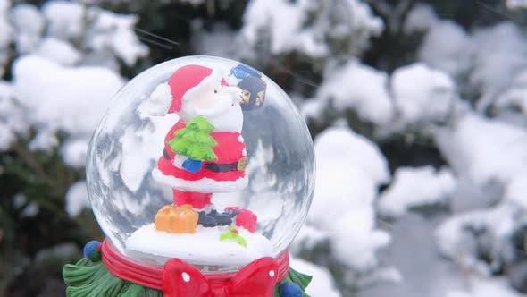 Halte verschneite Weihnachtskugel