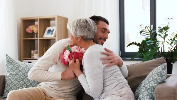 Cover Image for Adult Son Giving Flowers To Senior Mother at Home