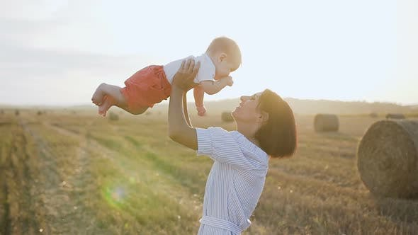 Thumbnail for Woman in a Light Dress Raises High up Her Charming Baby Boy