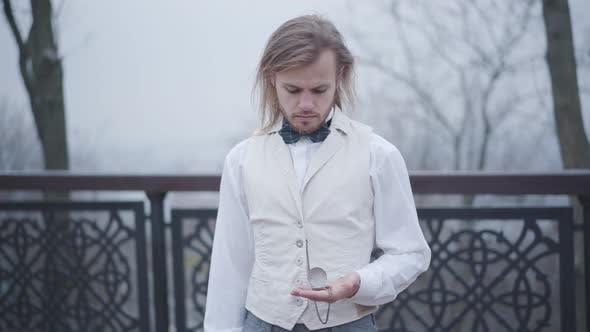 Thumbnail for Stylish Caucasian Guy with Long Hair and Beard Standing at Bridge and Checking Time on Vintage Hand