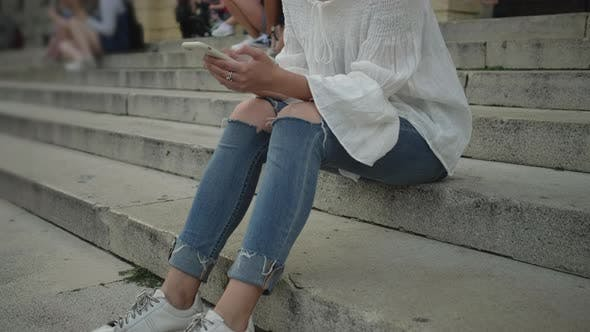 Mädchen mit Mobile sitzt auf der Treppe
