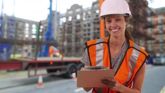 Thumbnail for Female construction worker on street by work site smiling at camera